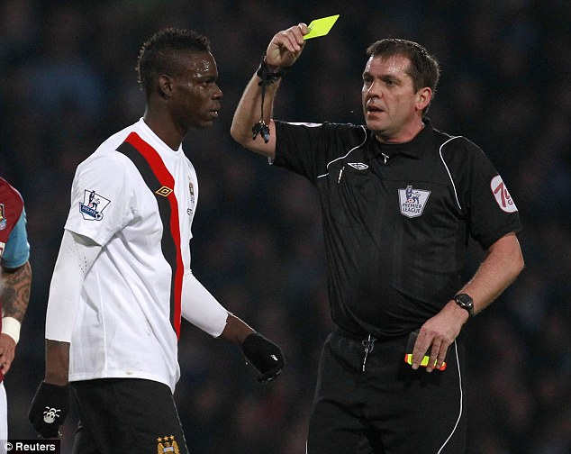 Yellow peril: Mario Balotelli is booked by referee Phil Dowd  at Upton Park