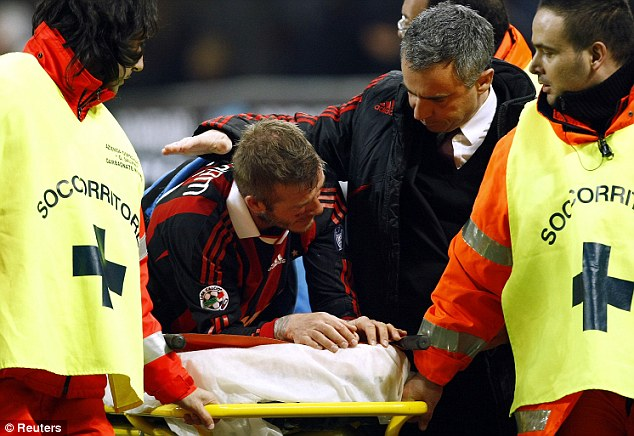Agony: David Beckham is assisted as he leaves the pitch during AC Milan's clash with Chievo