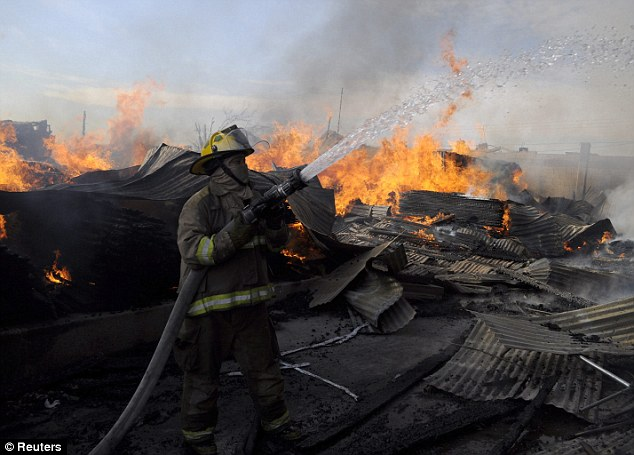 Arson: A firefighter tries to put out the fire at a warehouse owned by the husband of Marisela Escobedo, who was murdered last week