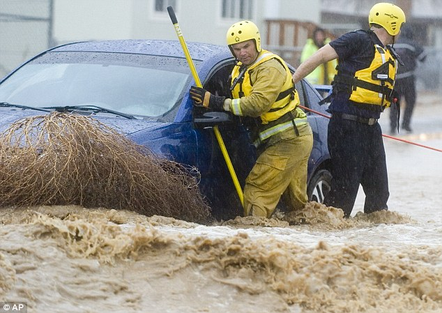 Rescue mission: Firefighters Jay Hausman, left, and Ryan Beckers, right, pull a motorist from a car caught in swift water at Hughes and Avalon Road in Victorville