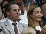 British actor Hugh Grant (L) sits on Centre Court to watch the men's singles final match between Serbia's Novak Djokovic and Switzerland's Roger Federer on day thirteen of the 2015 Wimbledon Championships at The All England Tennis Club in Wimbledon, southwest London, on July 12, 2015.  RESTRICTED TO EDITORIAL USE  --  AFP PHOTO / ADRIAN DENNISADRIAN DENNIS/AFP/Getty Images