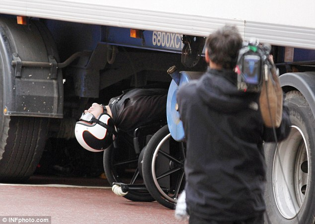Missing by an inch: The stunt double lays completely backwards as he travels underneath the lorry