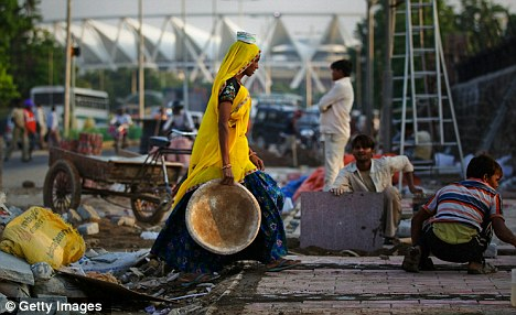Mucking in: Indian labourers scramble to complete last minute preparations for the upcoming Games