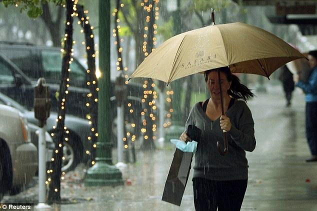 Dash: A shopper runs for cover as the rain continues to bucket down in Montrose, California