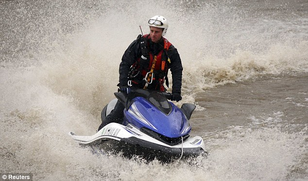 Swept away: A member of the Los Angeles Fire Department drives a watercraft in the LA River after two victims were reported to be swept away in the water today. The search eventually had to be called off due to the weather