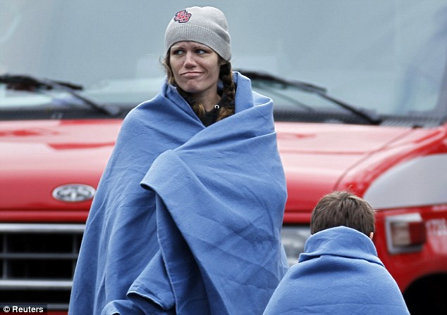 Call this a holiday? Guests are kept warm with blankets after they were rescued from their hotel