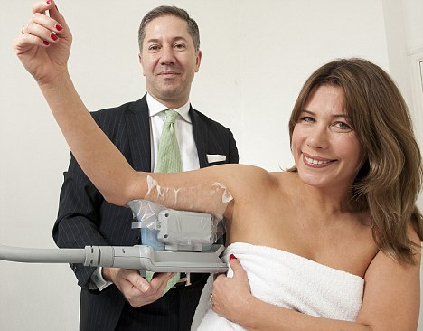 Chilling out: Leah Hardy is one of the first journalists to trial the new fat freezing treatment. Here Dr Mario Luca Russo gets to grips with her fatty bits using the CoolSculpting equipment