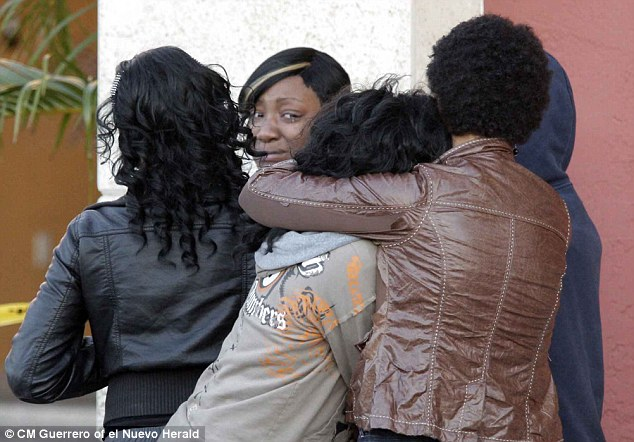 Breaking down: Family and friends in tears as the bodies are removed yesterday