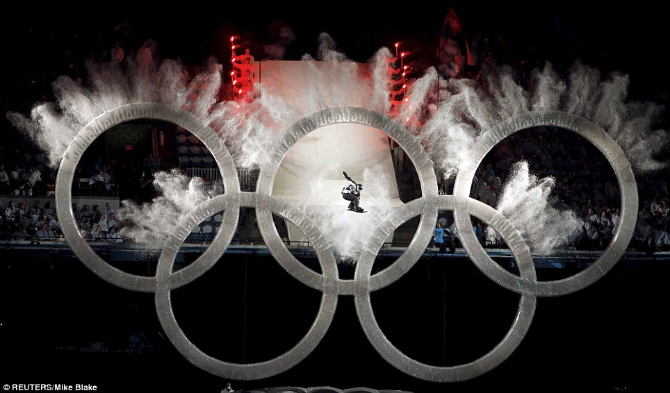 A snowboarder soars through the Olympic Rings during the opening ceremony of the Winter Olympics in Vancouver, Canada