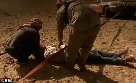 Man down: James May banged his head when he was knocked down by the rope towing Hammond's car out of the sand