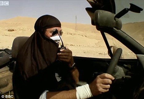 Incognito: Clarkson, seen here at the wheel of his car in Syria, had the idea to dress in a niqab in order to drive in disguise as they swapped the desert for a proper road
