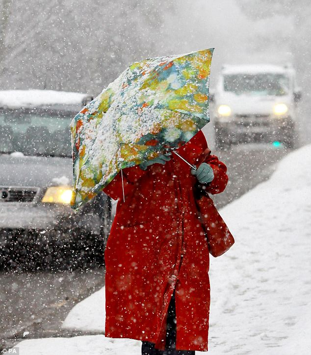 Not umbrella weather: A lady braves the elements in Ashford, Kent