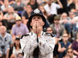 A British police officer reacts as he watches a giant screen showing the second set tie-break in the men's singles final match between Serbia's Novak Djokovic and Switzerland's Roger Federer, on day thirteen of the 2015 Wimbledon Championships at The All England Tennis Club in Wimbledon, southwest London, on July 12, 2015.  RESTRICTED TO EDITORIAL USE  -- AFP PHOTO / LEON NEALLEON NEAL/AFP/Getty Images