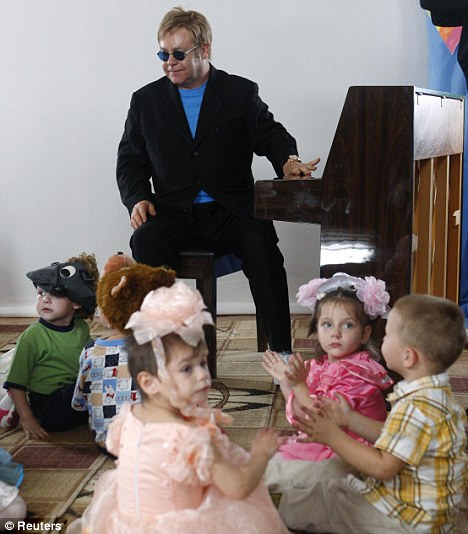 Father figure: Elton John on a visit to a hospital for HIV positive children. The singer now has a child of his own in Zachary Jackson Levon Furnish-John