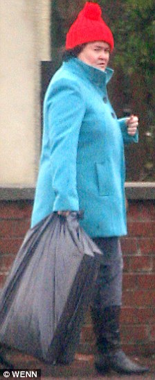 Down at the bottom of the garden: Susan Boyle could have been mistaken for a garden gnome as she stepped out in Blackburn in a blue coat and red hat