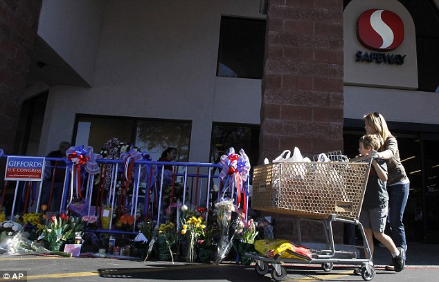 Never forget: A mother and her young son take in the memorial outside the Safeway as they leave with their shopping today