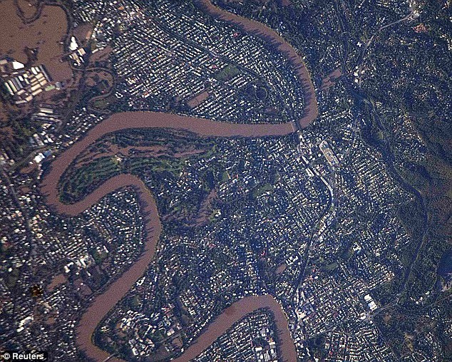 Flooded:The Brisbane River is seen swollen next to several suburbs in the southern part of Brisbane in this image taken two days ago by astronauts on board the International Space Station