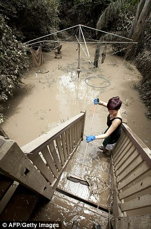 Aftermath: Alice Richter-Ward cleans the mud from her Ryan Street home in the West End area of Brisbane