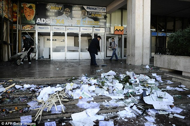 Aftermath: Workers clean a train station that was damaged over night amid the protests throughout the suburbs of Tunis