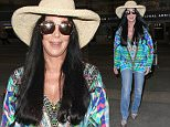 Cher wearing a colorful top and hat and jeans arriving at LAX from London in a great mood.  Sunday, July 12, 2015. X17online.com