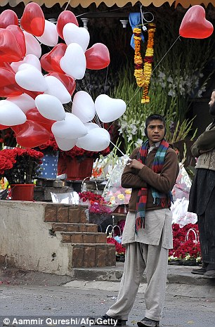 A Pakistani vendor holds heart-shaped balloons as he waits for customers on a street on the Valentines Day in Islamabad on February 14, 2011.