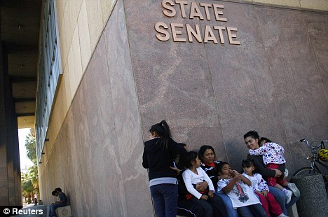 Anger: A family sits outside Arizona State Senate building during a protests against controversial immigration reforms