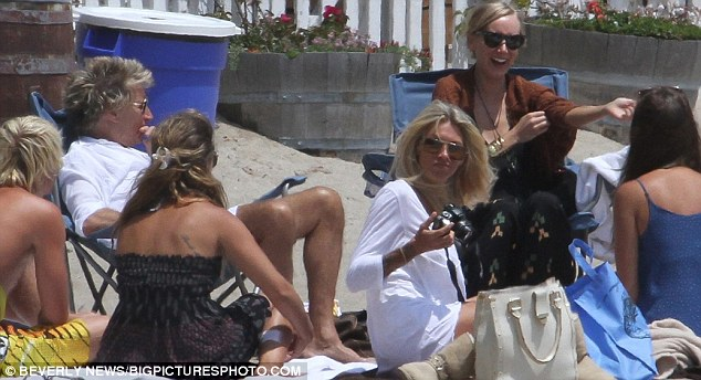 Family affair: Rod sits on a deckchair alongside wife Penny Lancaster, while Kimberly laughs and jokes