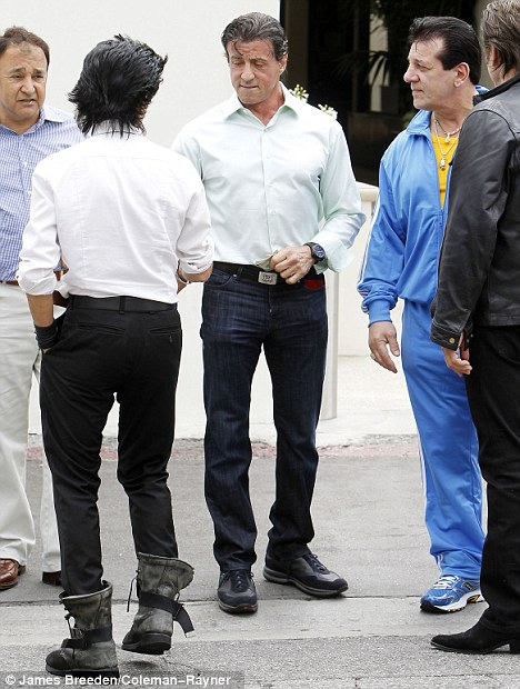 The men: Sylvester Stallone, centre, and a group of six male friends cheered up Arnold during their day out to lunch