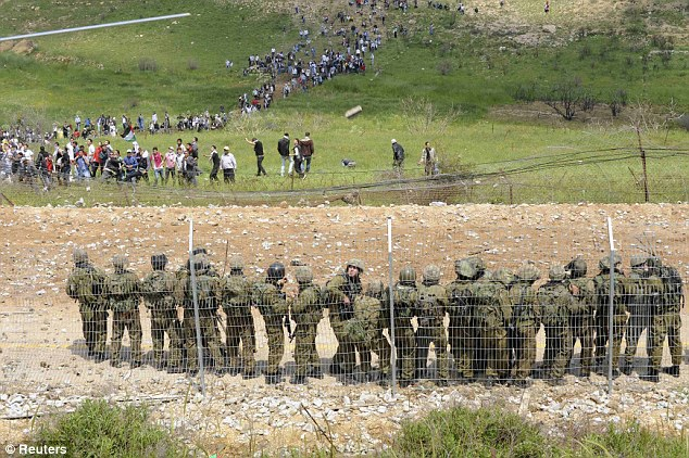 Hold the line: Israeli soldiers stand guard as Syrian protesters can be seen approaching the border line