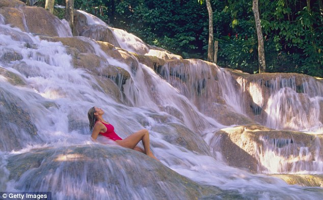A women is pictured sitting on a rock in her bathing costume at Dunn's River Falls