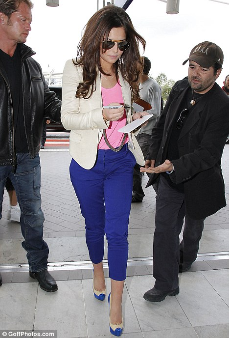 Can I have your autograph? Cheryl obliges a fan as she dashes through the terminal