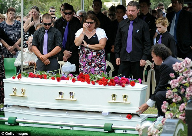 Sad day: The caskets are lowered at the Drayton and Toowoomba Cemetery