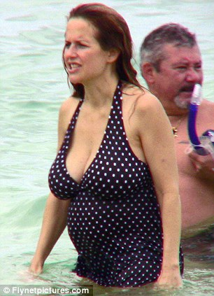 Taking a dip: Kelly cooled off in the sea in a navy blue halter neck swimsuit