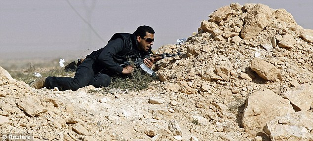Take cover: A rebel fighter protects himself during an attack by pro-Gaddafi forces along the Benghazi-Ajdabiyah road