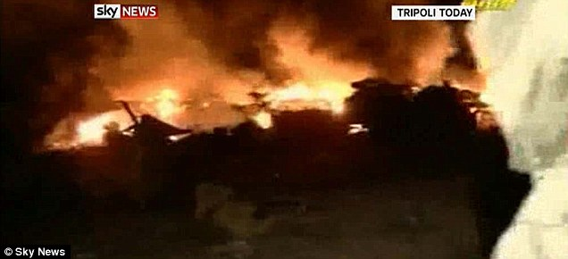 Aftermath: Television pictures show burning rubble and armoured vehicles following the 'coalition attacks'