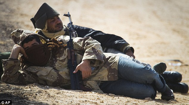 Take a break: Libyan rebels rest on a checkpoint on the frontline near Zwitina, the outskirts of the city of Ajdabiya, south of Benghazi