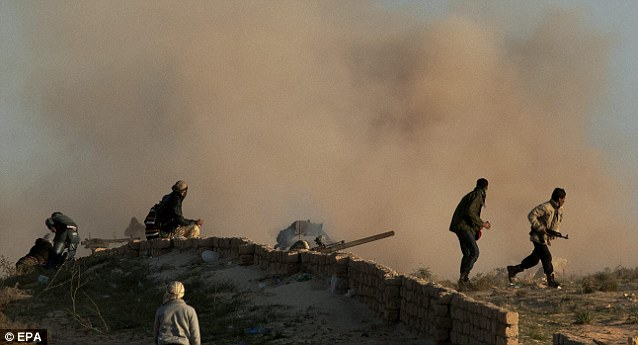 Blast: Rebels take cover after a blast during the siege of the eastern city of Ajdabiya