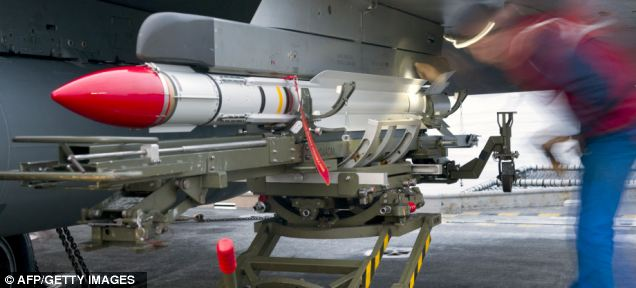 Weaponry: A mechanic mounts a Mica missile on a Rafale jet fighter on board the French aircraft carrier Charles de Gaulle during military operations in Libya