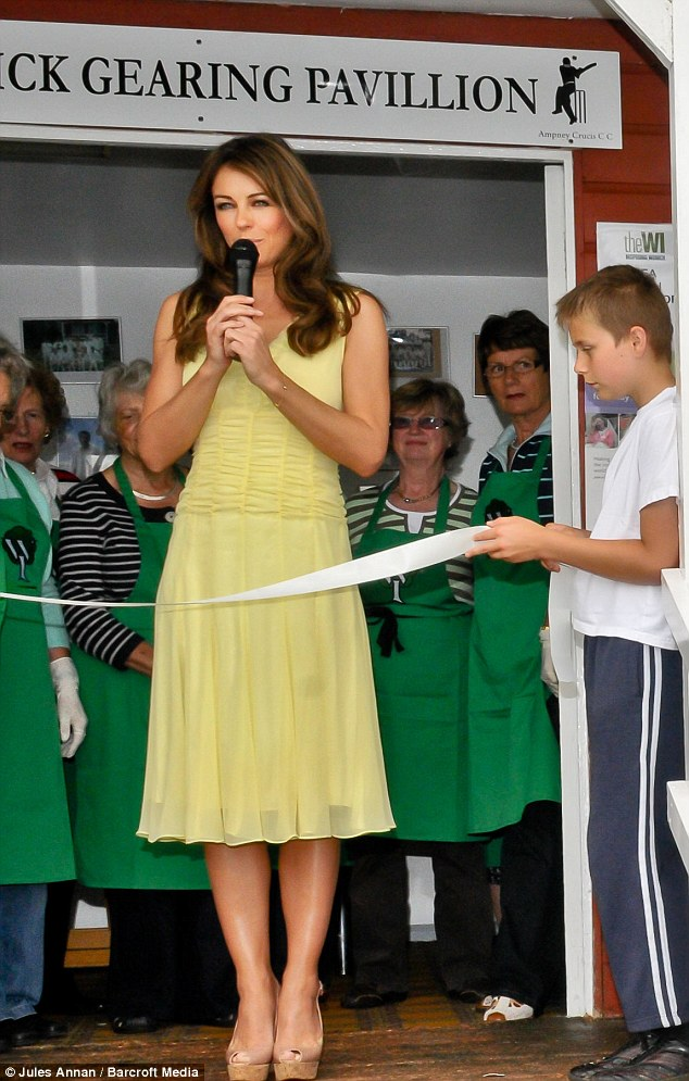 Star attraction: Liz Hurley, accompanied by boyfriend Shane Warne, was opening the Ampney Crucis Village Fete today near her home in Gloucestershire