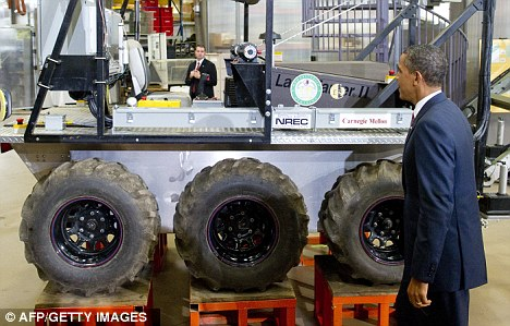 Mr Obama looks at a robot after speaking on technology and the economy and touring the National Robotics Engineering Center at Carnegie Mellon University in Pittsburgh, Pennsylvania yesterday
