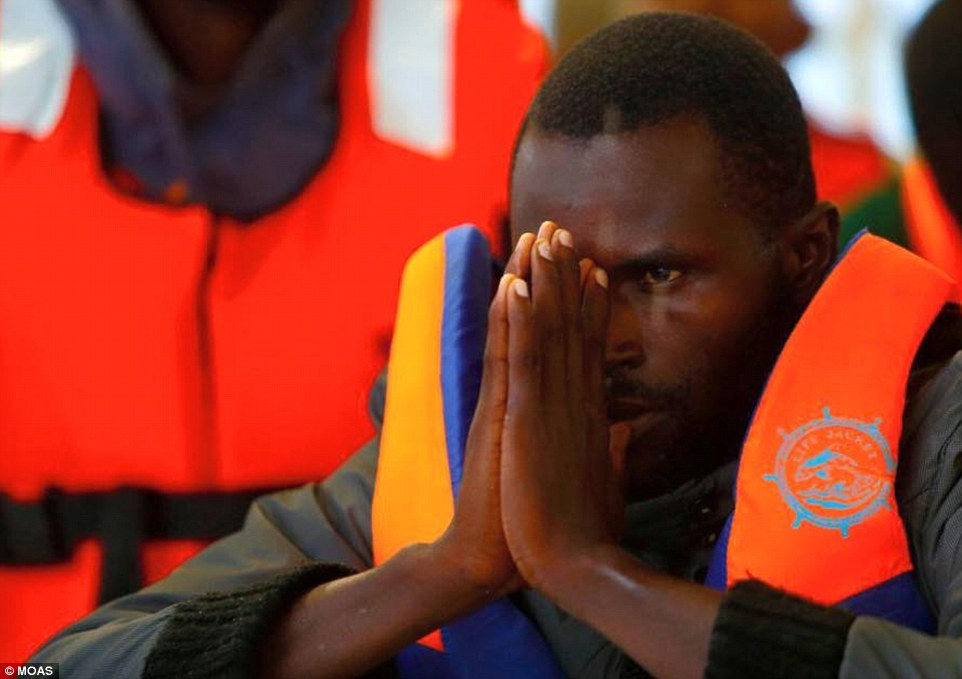 Thankful: The Phoenix's 'primary aim' is to 'reduce loss of life during dangerous migrant crossings from North Africa to Europe' - not to 'ferry migrants'. And it has certainly been fulfilling its aim so far - having saved 3,000 lives last year. Above, a rescued migrant prays