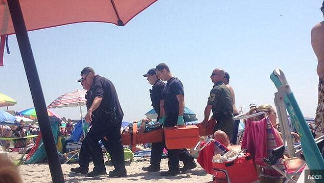 Baffled: Officials have admitted they have no idea what happened when a woman was catapulted into the air after an 'explosion' on a Rhode Island beach. She is pictured on a stretcher being taken to hospital