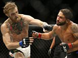 Conor McGregor, left, punches Chad Mendes during their interim featherweight title mixed martial arts bout at UFC 189 Saturday, July 11, 2015, in Las Vegas. (AP Photo/John Locher)