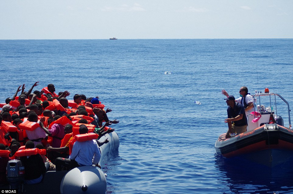 Rescue: The couple bought a former U.S. military training craft, two inflatable boats and two drones - and now spend their summers conducting search-and-rescue missions at sea. Above, two MOAS workers throw bottles of water to migrants from an inflatable boat