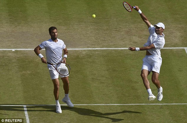 Romanian Tecau hits a smash during his straight sets win with Rojer against Peers and Murray