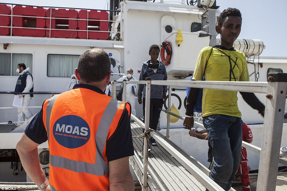 Disembarking: A young boy who had been stranded crossing from Africa to Europe looks at the camera as he disembarks the Phoenix