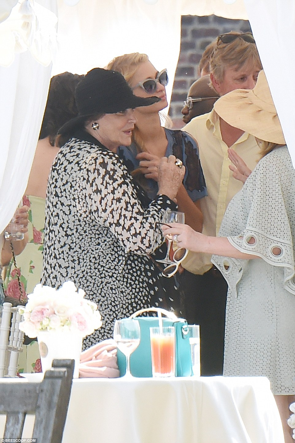 Deep conversation: The guest continues to stay close to Paris who looks almost under siege in the busy marquee