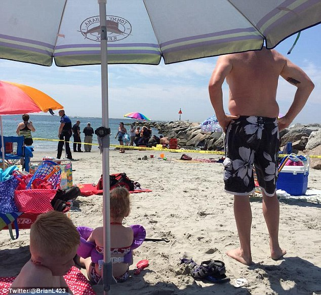 Cordoned off: Families at Salty Brine Beach watch as officials investigate the cause of the blast, which happened at around 11.15am on Saturday