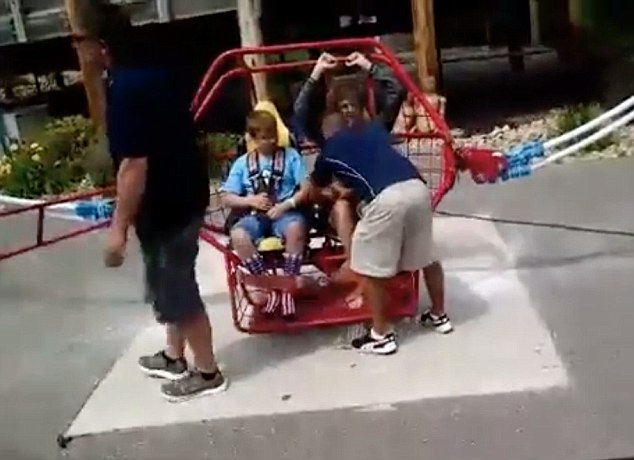 13-year-old Trevor Larson and family friend Carrie Sueker are strapped in place by workers in this video still