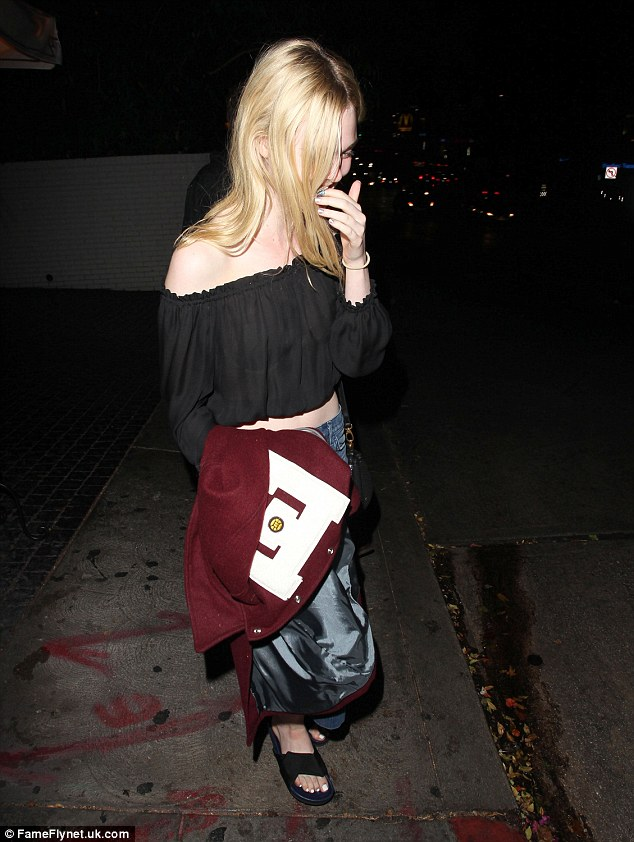 Toasty: Despite bring her midriff and both shoulders, the young actress felt warm enough not to wear the varsity jacket she was carrying
